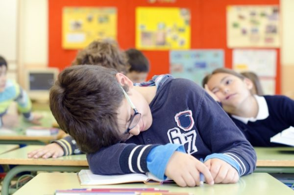 教科書枕にして寝ている少年
